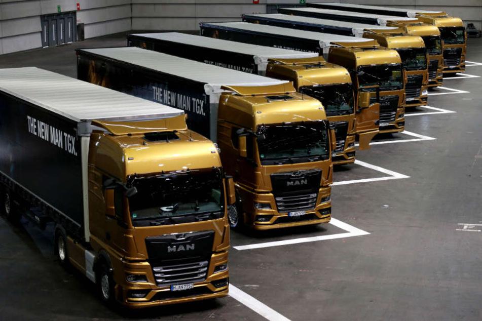 Neu entwickelte Lastwagen von MAN stehen während der Vorstellung der ersten Fahrzeuge in einer Halle.