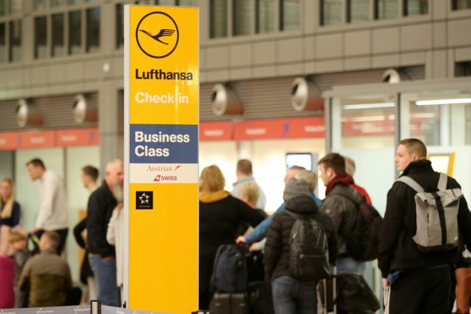 Reisende stehen am Flughafen Hamburg neben einem Lufthansa-Schild.