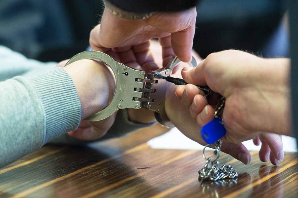 Ein Justizbeamter löst dem Angeklagten die Handschellen.
