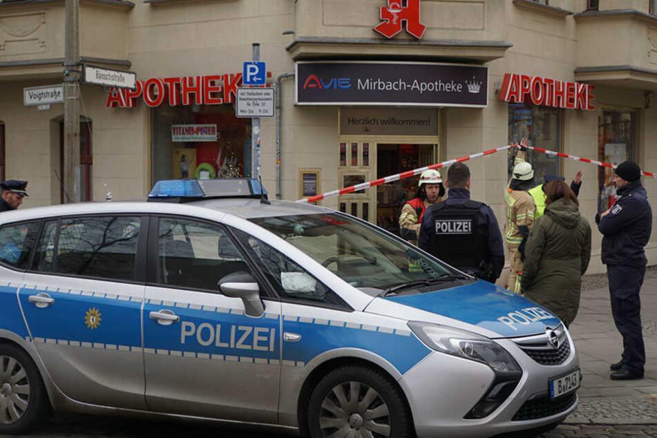 Polizisten sichern den Bereich rund um die Apotheke.