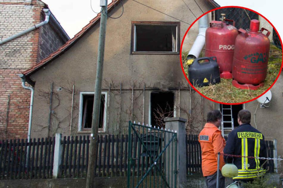 Einsatzkräfte der Feuerwehr stehen vor dem ausgebrannten Gebäude.