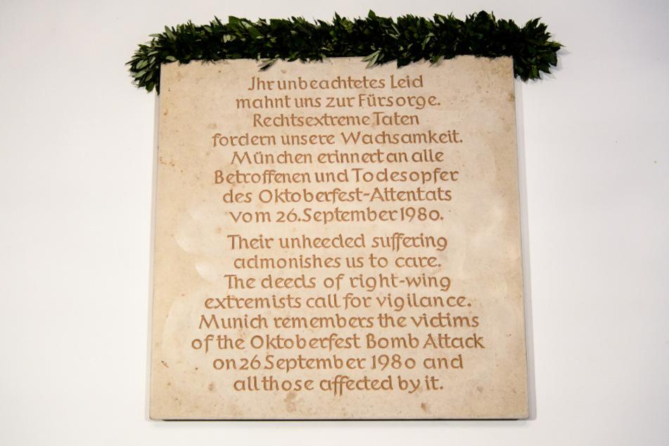 Eine Gedenktafel an das Münchner Wiesn-Attentat ist an einem Treppenaufgang im Rathaus zu sehen.