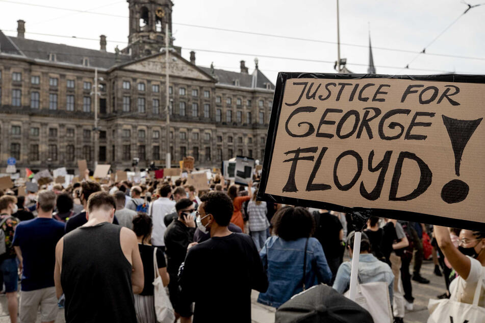"""Demonstranten halten während eines Protestes auf dem Dam ein Plakat mit der Aufschrift """"Justice for George Floyd"""" (Gerechtigkeit für George Floyd) in die Höhe."""