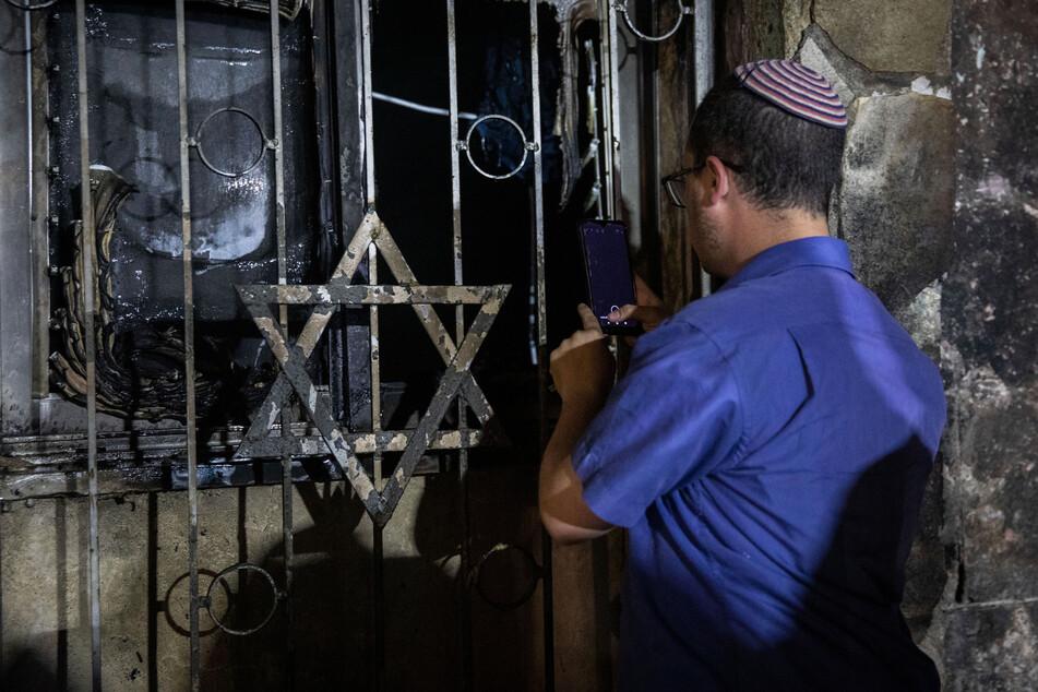 Ein israelischer Mann schaut in eine Synagoge, nachdem diese bei Zusammenstößen zwischen Juden und Arabern inmitten gewalttätiger Unruhen in der gemischt israelisch-arabischen Stadt Lod in Brand gesetzt wurde.