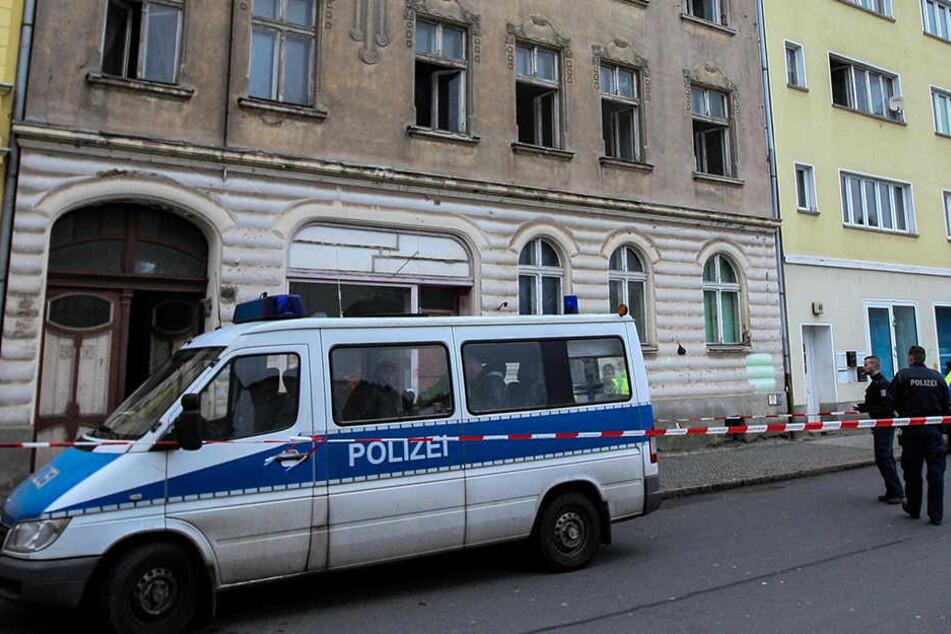 Die Polizei steht vor dem Mehrfamilienhaus in Rathenow, in dem die Feuerwehr nach einem Brand zwei Leichen entdeckt hat.