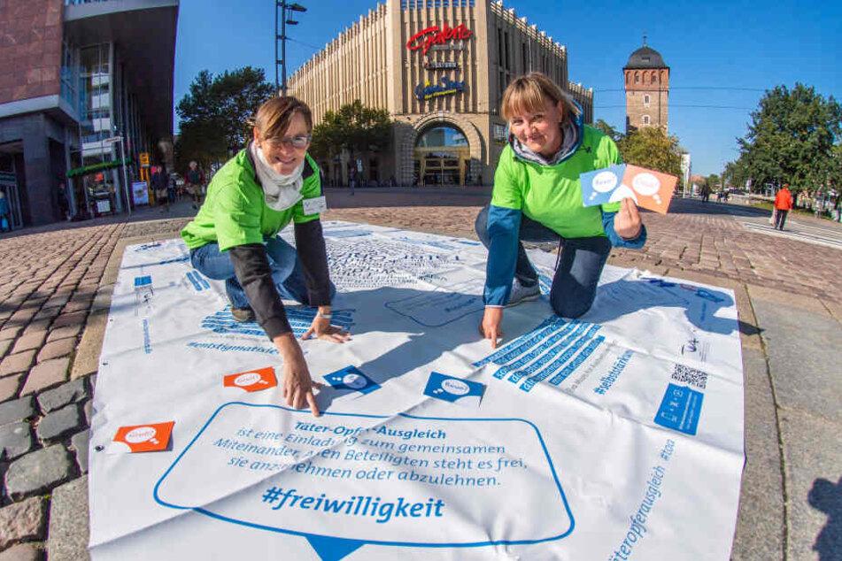 Ina Bannert (43) und Anja Hentschel (42) informieren mit einer Bodenzeitung über den Täter-Opfer-Ausgleich.