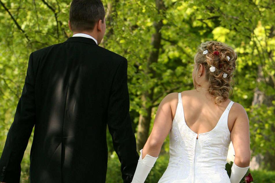 Ein Brautpaar geht nach der Trauung durch den Park. Hochzeitsfeiern in der Stadt scheinen nicht romantisch genug zu sein. (Symbolbild)