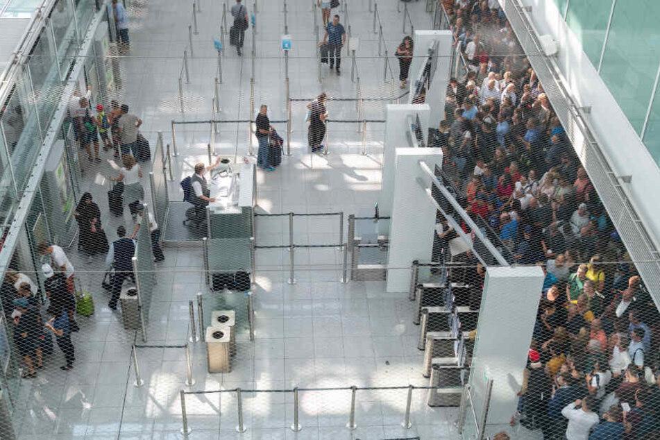 Die ersten Fluggäste betreten nach stundenlanger Sperrung den Sicherheitscheck-Bereich des Terminal 2 im Münchner Flughafen.