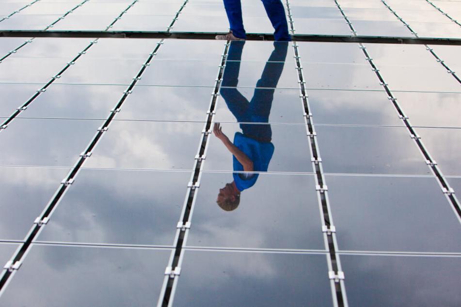 Ein Elektriker läuft für Wartungsarbeiten über ein Dach mit Solarplatten (Symbolbild).
