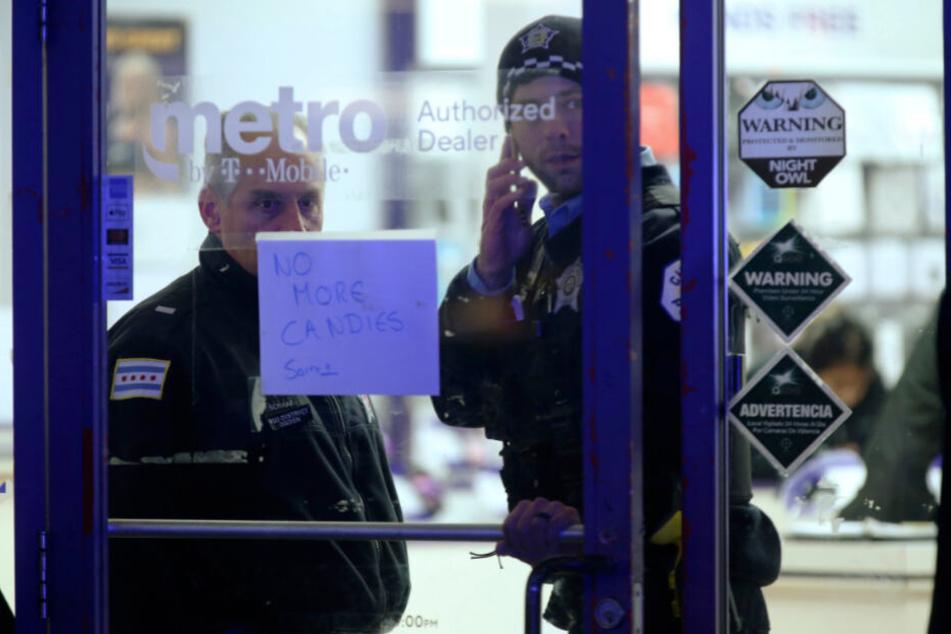 Zwei Polizisten stehen in einem Handy-Geschäft in der Nähe des Tatorts in Chicago.