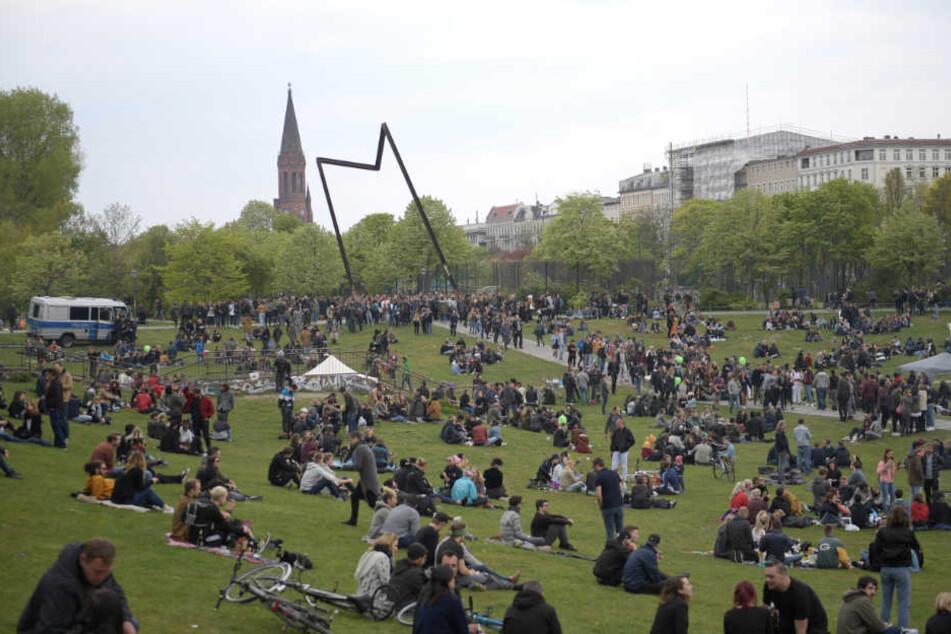 Zahlreiche Menschen sitzen im Görlitzer Park in Kreuzberg.