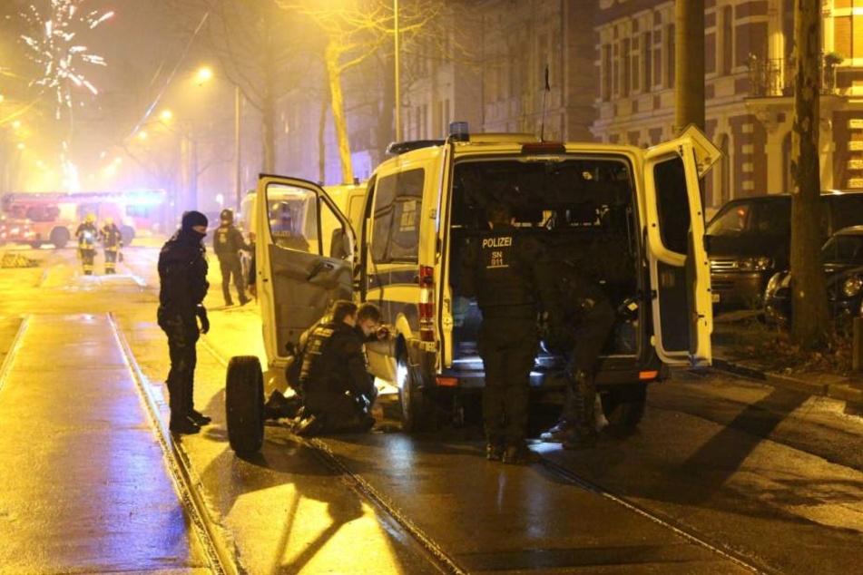 """Einsatzkräfte der Polizei beim Reifenwechsel. Mehrere Fahrzeuge von Polizei und Feuerwehr waren bei dem Einsatz durch sogenannte """"Krähenfüße"""" beschädigt worden."""