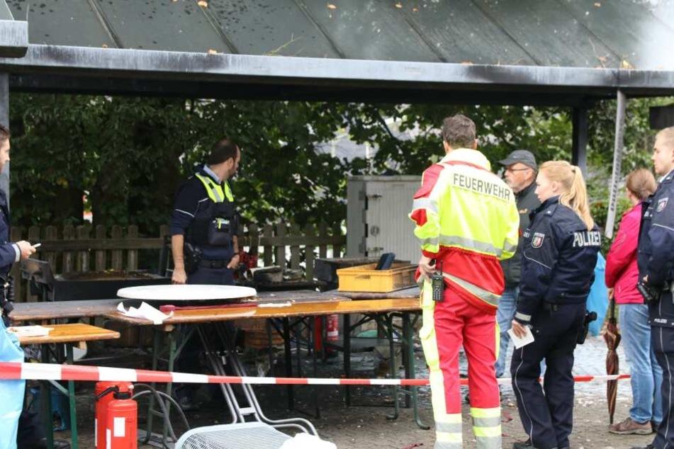 Polizisten und Feuerwehrleute stehen nach dem Unglück auf dem Gelände eines Brauchtumsfest im Siegerland.