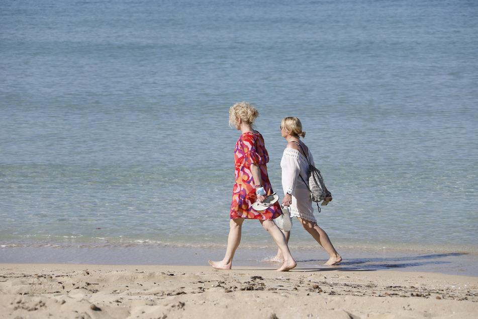 Zwei Frauen gehen am Strand von Arenal am Wasser entlang.