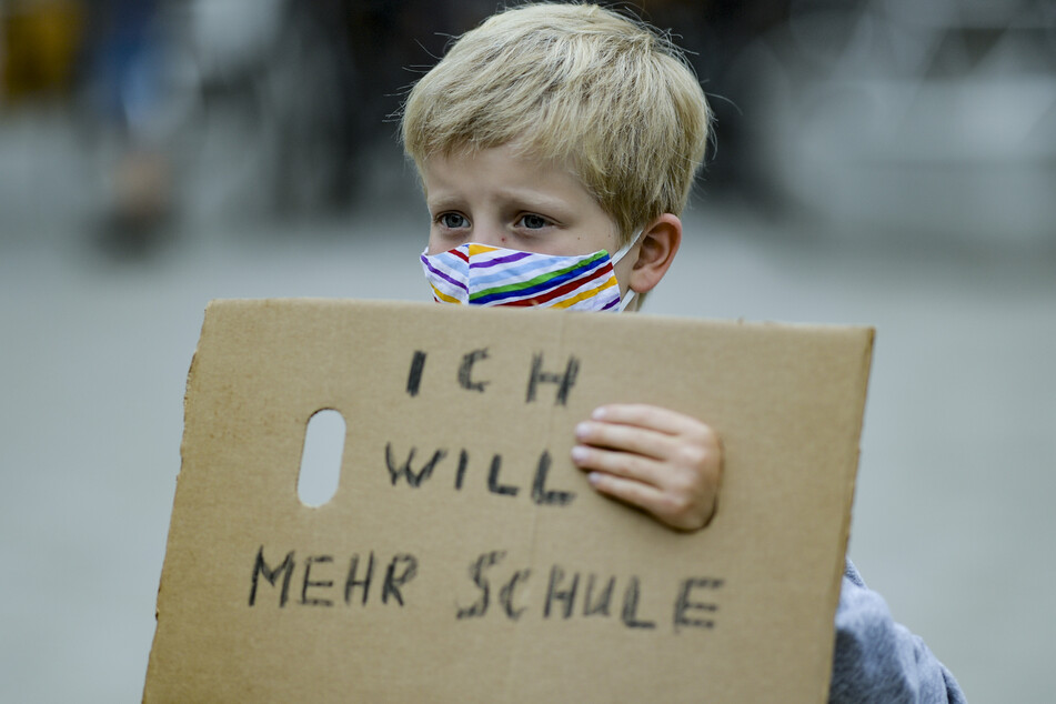 """Ein Junge trägt einen Mund-Nasenschutz, während er ein Stück Pappkarton mit der Aufschrift """"Ich will mehr Schule"""" auf dem Gänsemarkt vor sich hält."""