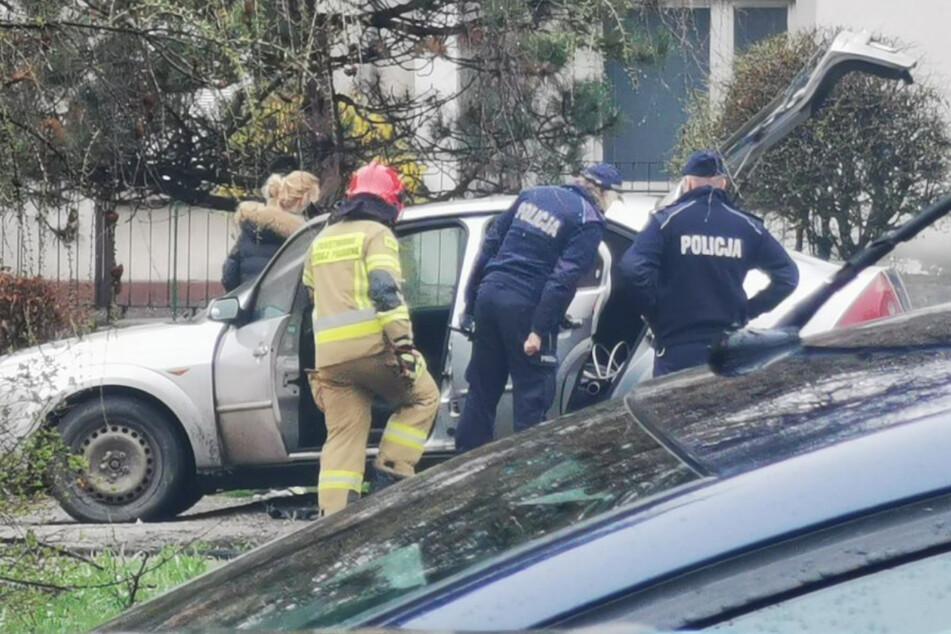 Polizisten und ein Feuerwehrmann begutachten das teilweise verbrannte Auto.