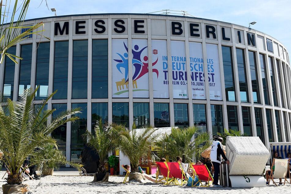 Besucher des Deutschen Turnfestes sitzen am letzen Tag der Veranstaltung, auf einer Strandlandschaft vor den Gebäuden des Messe in Berlin.