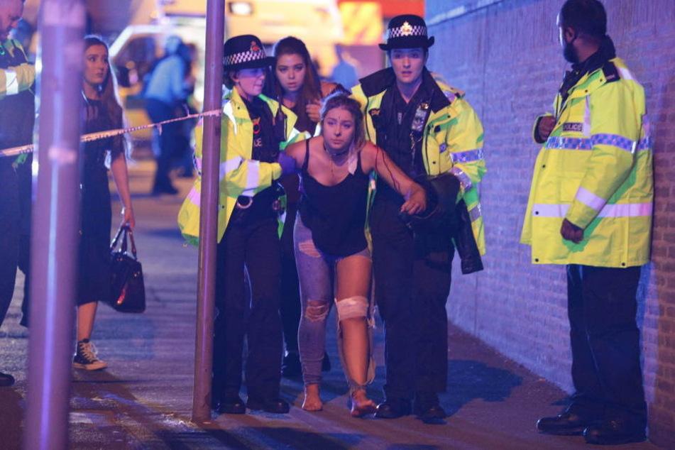 Rettungskräfte bringen die verletzten Opfer aus der Arena.