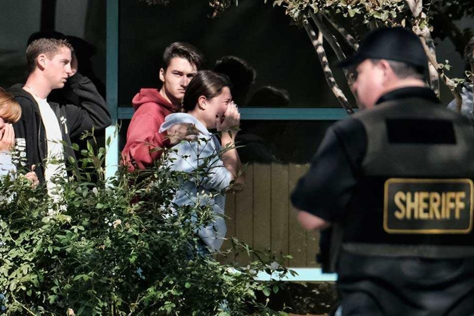 Trauernde werden in das Thousand Oaks Teen Center geführt, wo sich Familien nach einer tödlichen Schießerei in einer Bar versammelt haben.