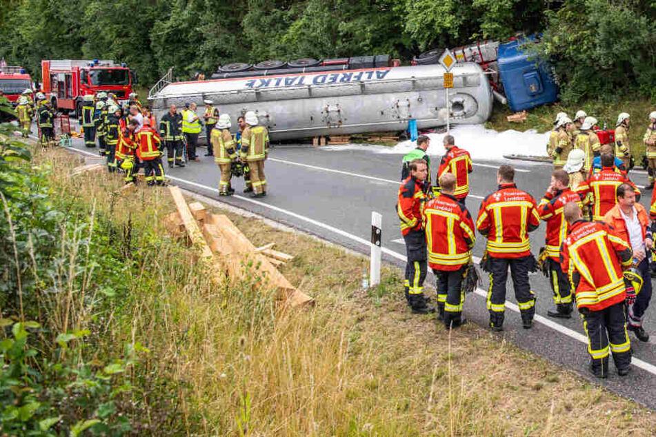 Einsatzkräfte der Feuerwehr und der Polizei stehen am Unfallort.