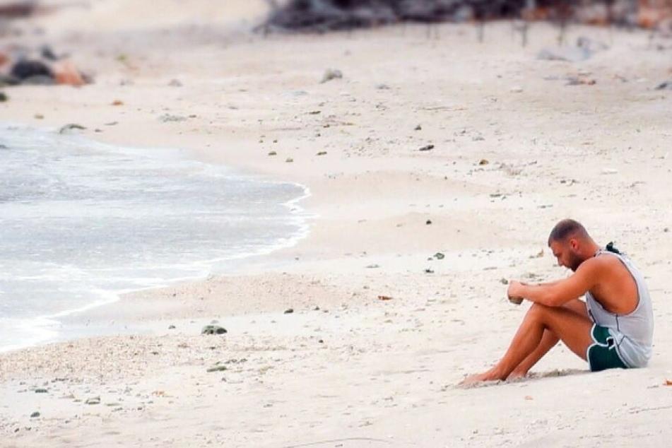Nachdenklich sitzt der 25-Jährige am Strand.