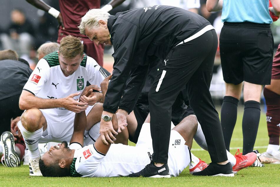 Gladbach-Angreifer Alassane Plea (28, u.) wälzte sich verletzt auf dem Boden. Anschließend musste er vom Feld getragen werden.