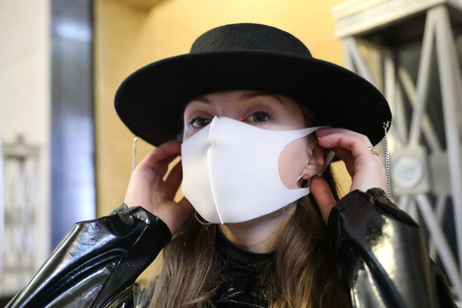 Eine Besucherin trägt eine Gesichtsmaske der Modemarke kARTu.