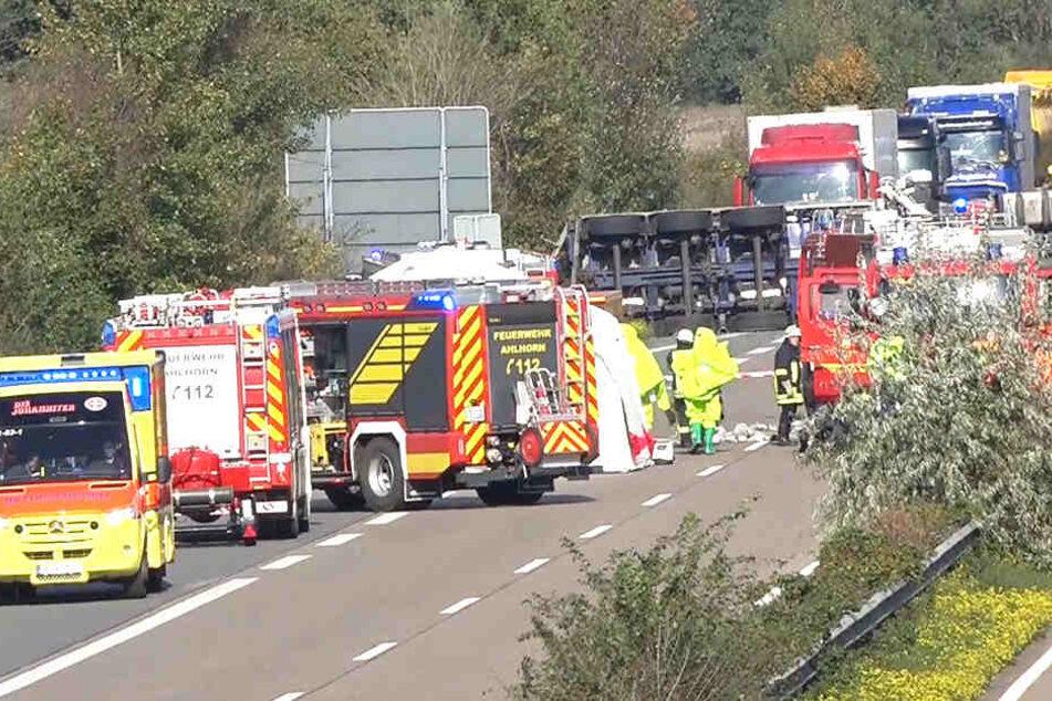 Rettungskräfte stehen um einen umgekippten Gefahrguttransporter herum, der auf der A29 liegt.