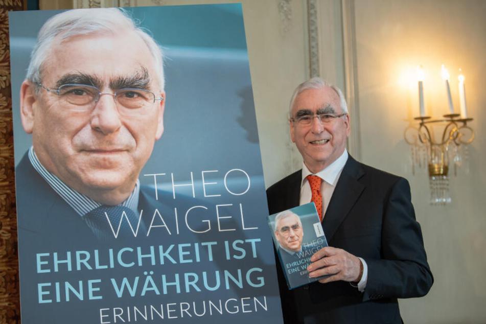 Theo Waigel steht vor Beginn der Pressekonferenz zur Vorstellung seiner Autobiografie neben einem Plakat und hält sein Buch in der Hand.
