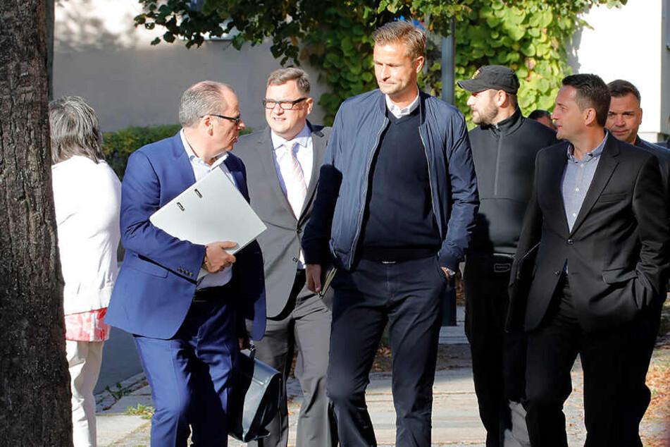 Trautes Quartett: Insolvenzverwalter Klaus Siemon (v.l.), Vorstand Thomas Uhlig, Trainer David Bergner und Sportchef Thomas Sobotzik, begleitet von zwei Sicherheitsleuten, auf dem Weg zum Amtsgericht.