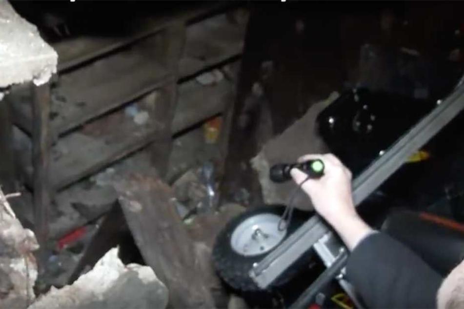 Unter dem eingestürzten Garagenboden tat sich ein weiterer Raum aus. Hier sind die  verstaubten Regale zu erkennen (li.)