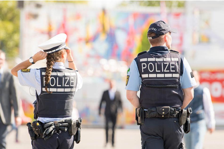 Polizeibeamte gehen bei der Eröffnung des 172. Cannstatter Volksfests in Stuttgart (Baden-Württemberg) über das Volksfestgelände.
