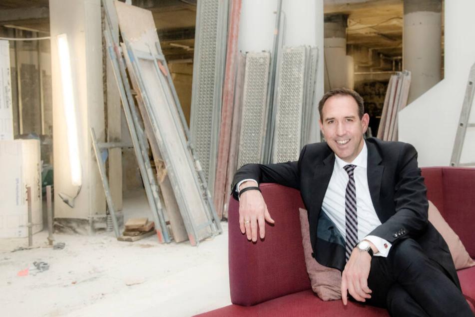 Hotel-Direktor Hannes Dreher sitzt auf einem roten Sofa auf der Baustelle.
