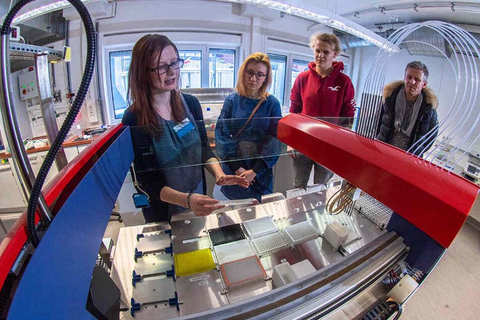Im Biotechnologie-Labor der HS Mittweida erklärt Dominique Tuch (30, l.) Jessica Kurucz (18), ihrem Vater Jörg Poetzsch (49) und Sören Tara (18) einen Roboter.