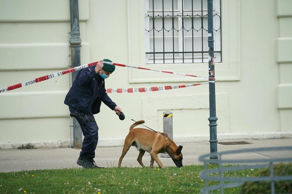 Ein Polizist ist vor der Wiener Hofburg mit einem Spürhund auf der Suche nach einer Bombe.
