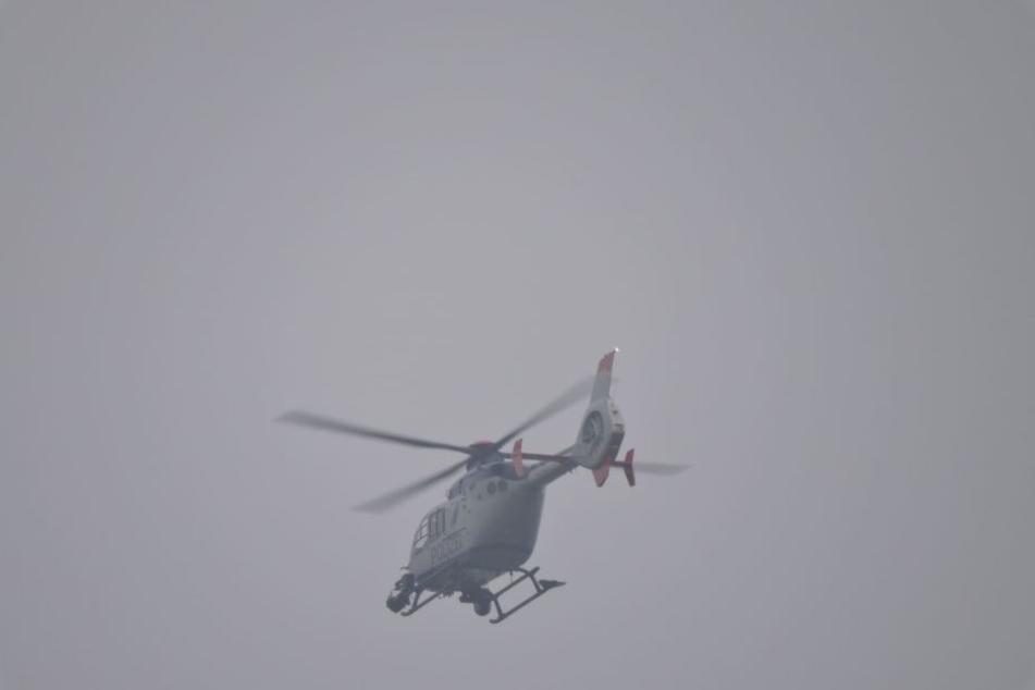 Ein Hubschrauber beobachtet das Geschehen in Zwenkau aus der Luft.