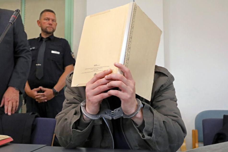 Der angeklagte Stiefvater hält sich eine Mappe vor das Gesicht.