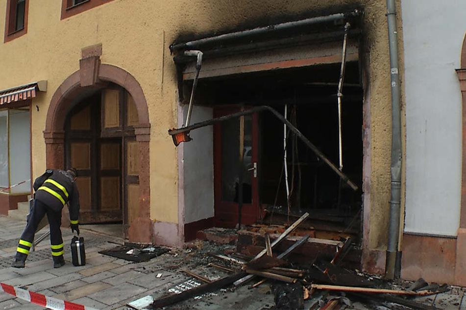Die Brandursachenermittler der Polizei untersuchen den vom Feuer zerstörten Laden.