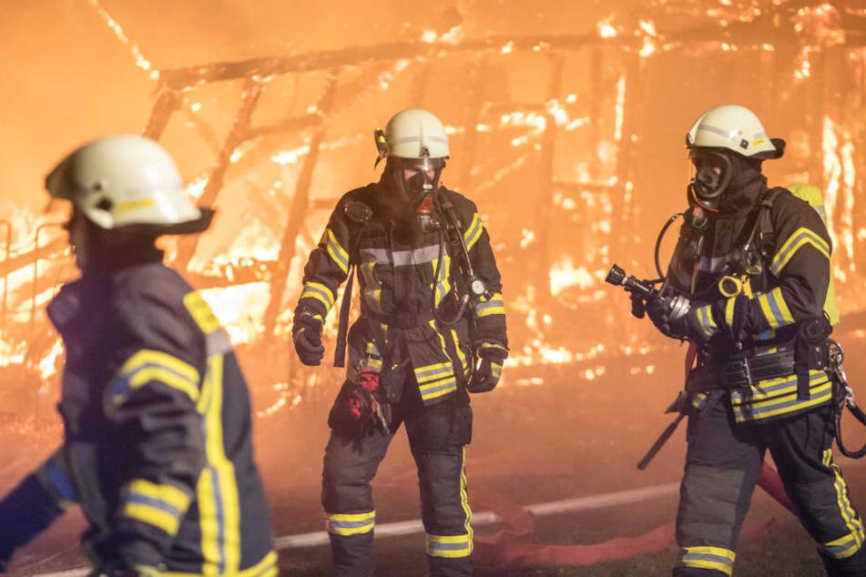Feuerwehrleute laufen an den brennenden Resten der Halle vorbei.