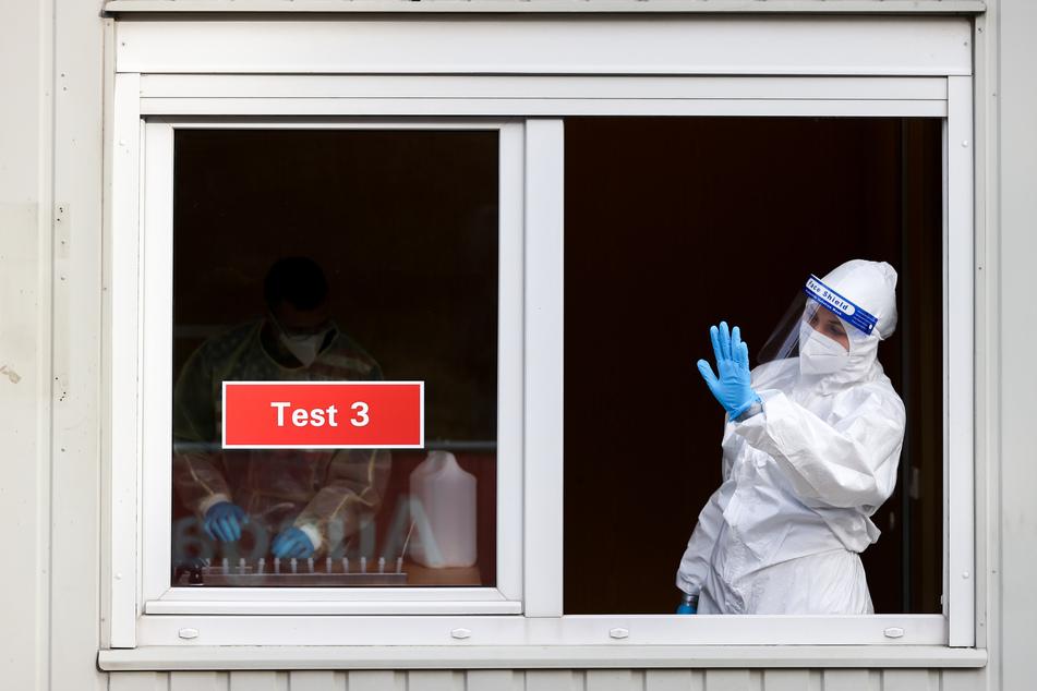 Sachsen, Augustusburg: Eine Frau in Schutzkleidung winkt Testwillige zu ihrem Fenster an einem Testcenter. Nach Ostern sank die Inzidenz in Deutschland leicht. Doch vielerorts wurden weniger Tests durchgeführt.