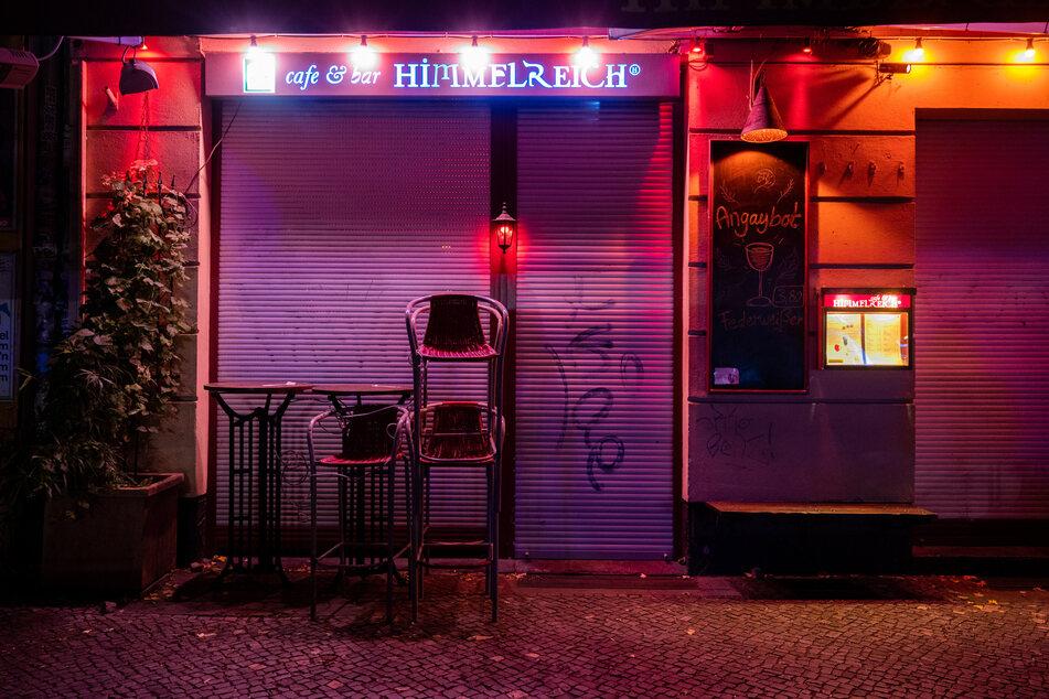 Vor einer Bar im Berliner Stadtteil Friedrichshain sind Stühle übereinander gestapelt. Wegen der Corona-Pandemie gelten eine nächtliche Sperrstunde und strengere Kontaktverbote für drinnen und draußen.