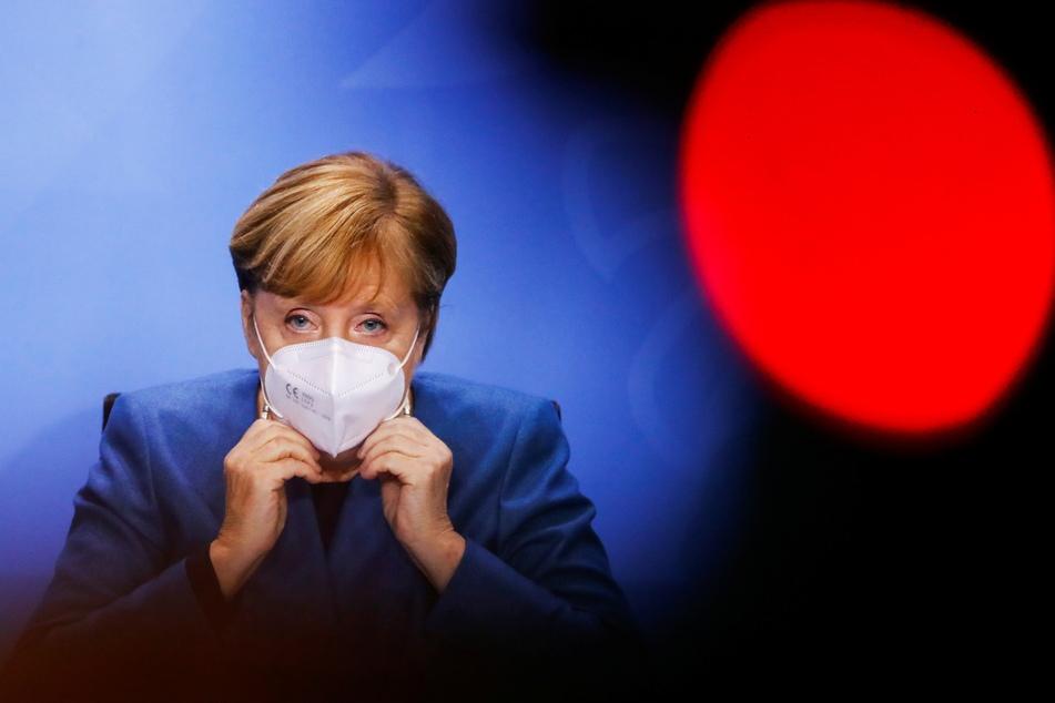 Bundeskanzlerin Angela Merkel (CDU, 66) setzt am Ende einer Pressekonferenz, nach einem Treffen mit den Ministerpräsidenten der Länder zum weiteren Vorgehen in der Corona-Pandemie, ihre Maske auf.