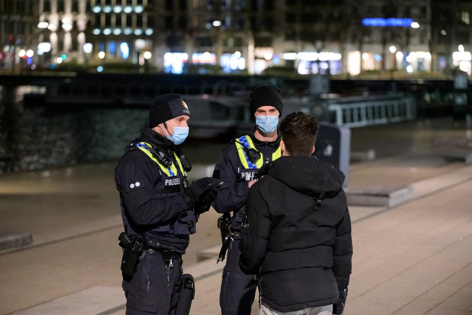 Polizisten kontrollieren am Jungfernstieg einen Mann, der sich nach 21 Uhr im Freien aufhält.