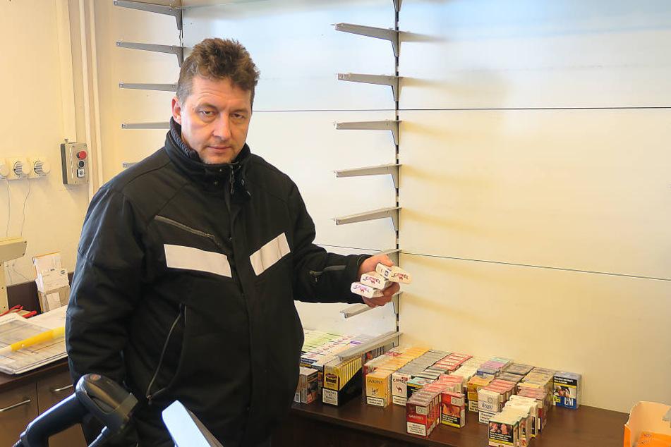 Pächter Jan Jacob vor dem leeren Zigarettenregal in sein er Tankstelle.
