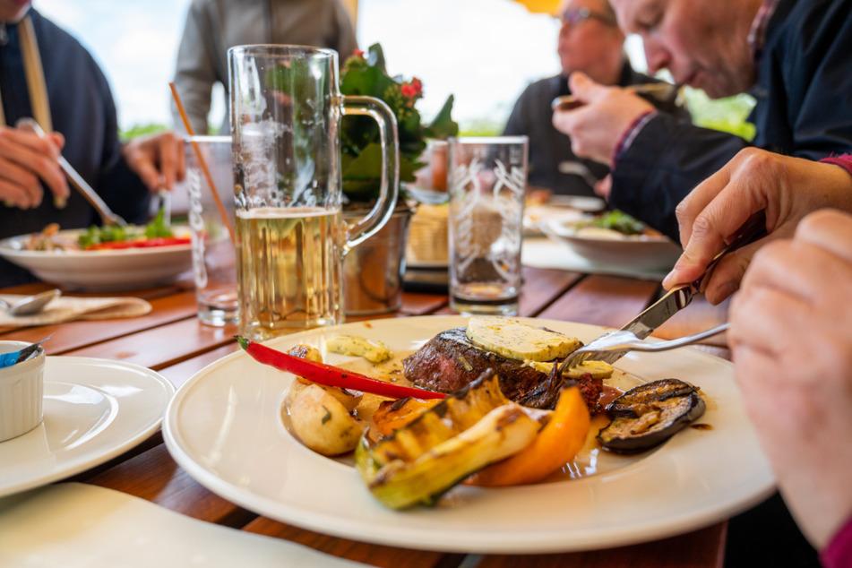 Gäste essen in einem Restaurant. Wegen der neuen Corona-Verordnung in Thüringen müssen keine Termine mehr für Besuche im Biergarten oder für die Außengastronomie vereinbart werden. (Symbolbild)