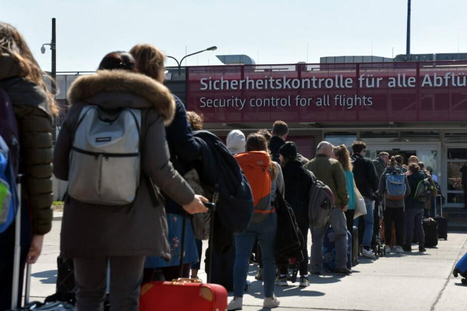 Reisende warten vor der Sicherheitskontrolle.