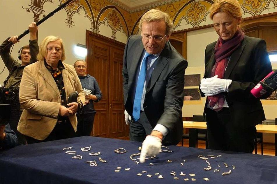 Der Leiter des Archäologischen Landesamts, Claus von Carnap-Bornheim (M.) und Kulturministerin Karin Prien (CDU, re) schauen sich den Silberschmuck an.