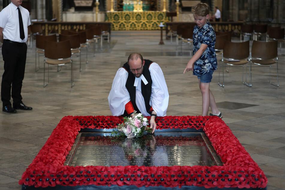 Pfarrer Anthony Ball (M) legt nach der Hochzeit von Prinzessin Beatrice von York den Brautstrauß gemäß einer Tradition auf das Grab des Unbekannten Soldaten in der Westminsterabtei.