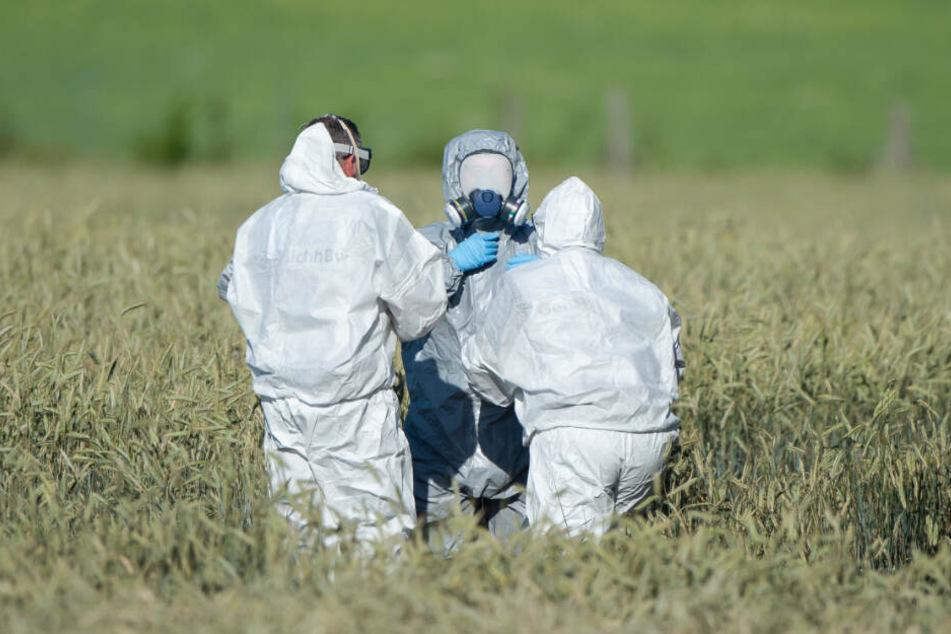 Mitarbeiter der Flugsicherheit der Bundeswehr helfen einem Mitarbeiter aus dem Schutzanzug, der auf einem Feld Wrackteile untersucht hat.
