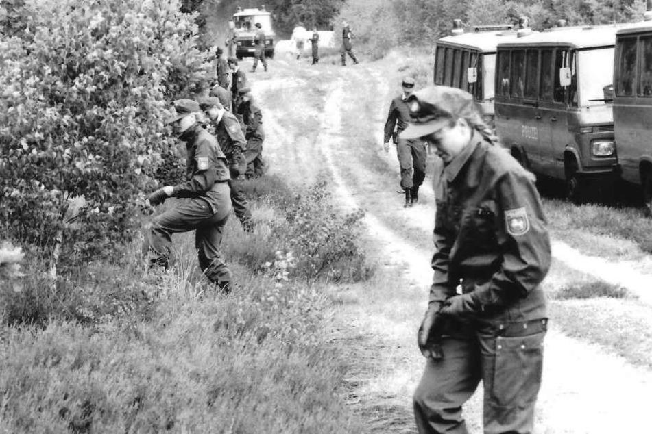 Polizeibeamte durchsuchen im Juli 1989 den Wald in der Göhrde nach einem Doppelmord.